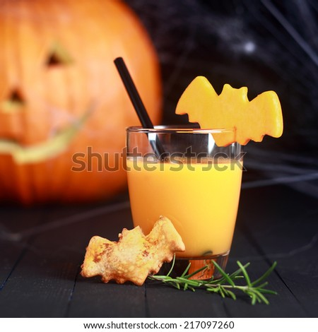 Halloween orange juice served in a glass with a straw garnished with flying bats and a bat cookie standing in front of a pumpkin jack-o-lantern on a dark background, square format - stock photo
