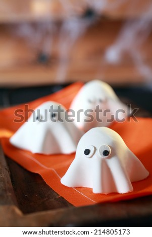 Halloween party decorations from folded pastry dough in the shape of scary little ghosts with big eyes on an orange napkin with copyspace for your greeting or invitation