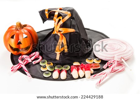 Halloween party decorations with carved pumpkins, marshmallows and witch hat - stock photo