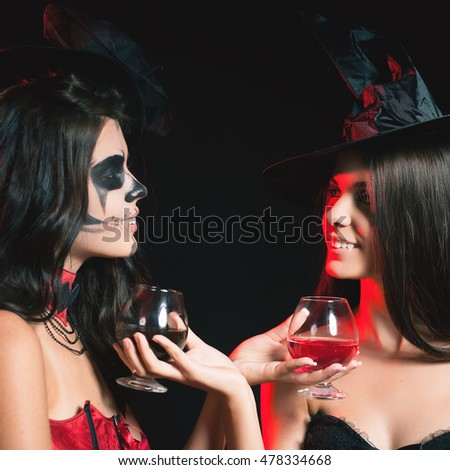 Halloween party 2016! Fashion women like witch holding cocktail of blood. Makeup. Halloween costumes. Role. Witch carnival costume