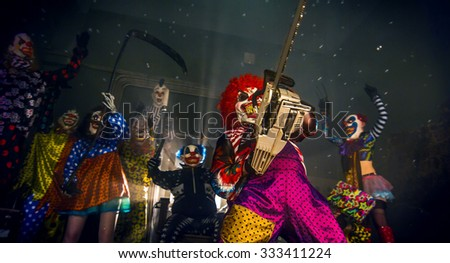 Halloween party horror clowns. The clown in the red wig standing with a chainsaw. - stock photo
