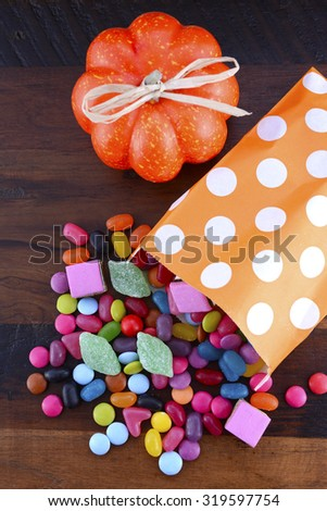 Halloween Party Trick of Treat Candy with candy flowing from orange polka dot party favor bag on dark wood background.  - stock photo