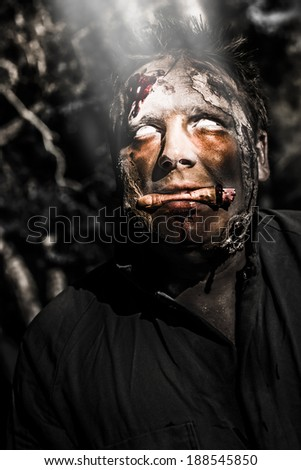 Halloween portrait of a bleeding psychotic horror zombie looking to the netherworld light when chewing on a human finger.  - stock photo