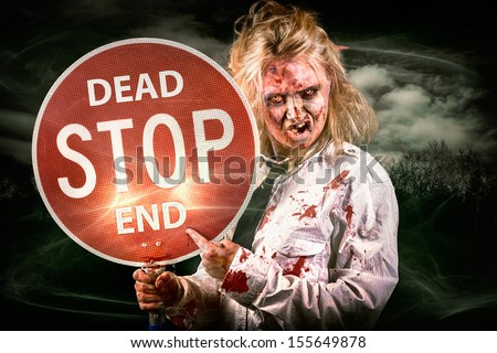 Halloween portrait of a scary zombie holding stop sign in a spooky field during night in a depiction of a dead end