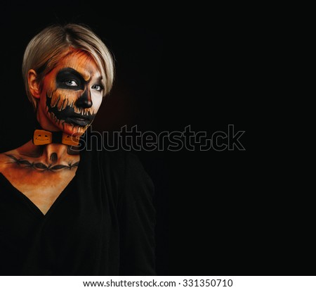 halloween portrait of body art pumpkin girl with pumpkin bowtie on black background. Real greasepaint and face art makeup
