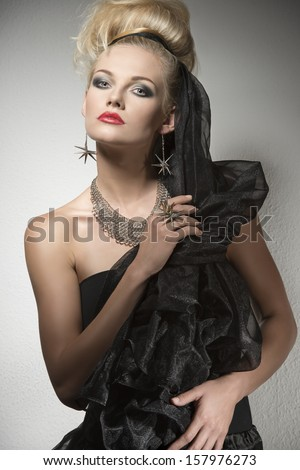 Halloween portrait of cute blonde girl with dark elegant dress and creative make-up and hair-style. Wearing silver accessories and looking in camera