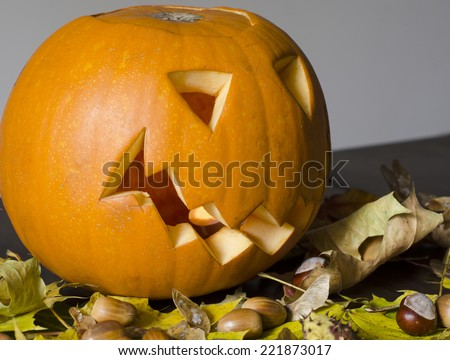 Halloween pumpkin among the autumn leaves and chestnuts