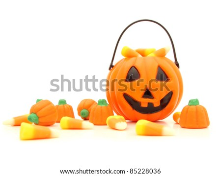 Halloween pumpkin and a pile of scattered assorted candies against a white background - stock photo