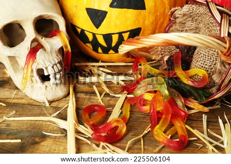 Halloween pumpkin and candies in basket on wooden table background - stock photo