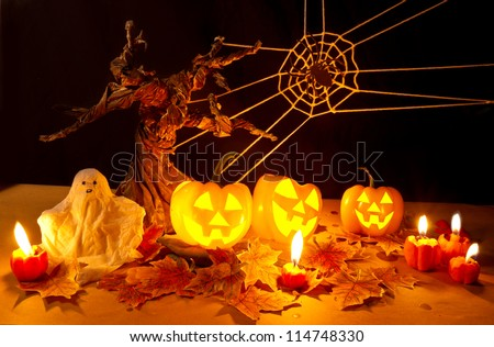 Halloween pumpkin and ghost under spooky tree - stock photo