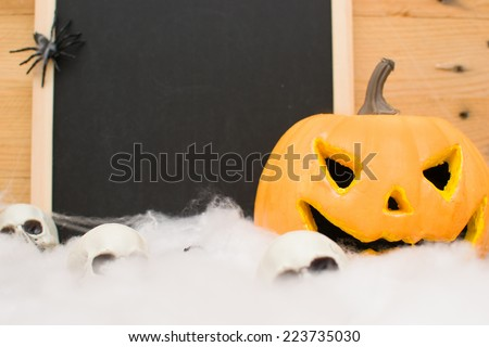 Halloween pumpkin and skull in a fireplace - stock photo