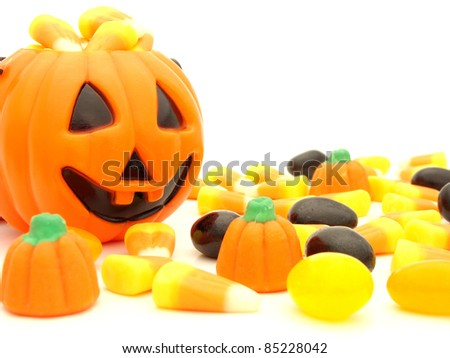 Halloween pumpkin behind a pile of scattered assorted candies against a white background - stock photo