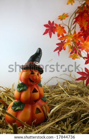 halloween pumpkin figure with straw and colored autumn leaves