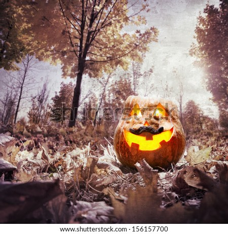 Halloween pumpkin glowing inside in dark autumn park - stock photo