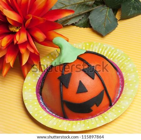 Halloween pumpkin head cake with orange flower - stock photo