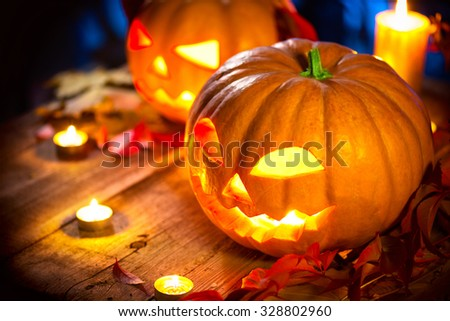 Halloween pumpkin head jack lantern with burning candles over wooden background. Halloween holidays art design, celebration. Carved Halloween Pumpkins with burning candles - stock photo