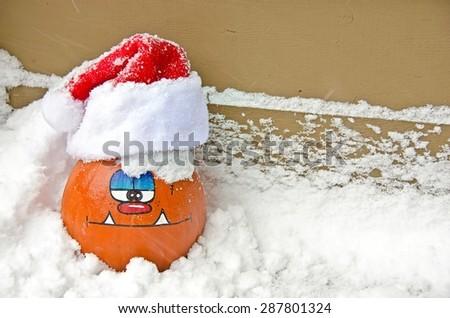 Halloween pumpkin in snow with Santa cap - stock photo