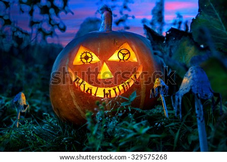 Halloween pumpkin in the garden at night with the eyes of the gears of the clock with the teeth of the metal parts between the fabulous fungi. - stock photo