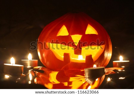 halloween pumpkin jack-o-lantern candle lit, isolated on black background