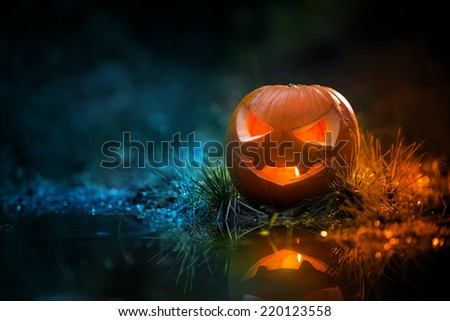 Halloween pumpkin lantern with burning candle inside and water reflection in a dark forest. - stock photo