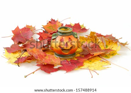 Halloween Pumpkin Lantern with yellow and red autumn leaves - stock photo