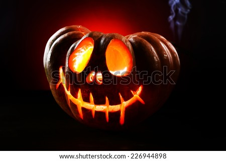 Halloween pumpkin on table on dark red background - stock photo