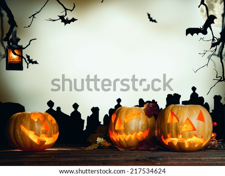 Halloween pumpkin on wooden planks. Cemetery grave stones on background - stock photo