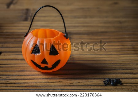 Halloween pumpkin on wooden with a spider - stock photo