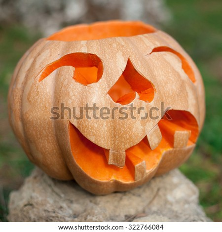 Halloween pumpkin outdoor. Creepy carved pumpkin face on open air - stock photo