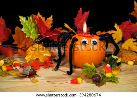 Halloween pumpkin spider candle with acorns and candy corn in autumn leaves - stock photo