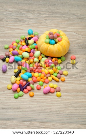 Halloween pumpkin that is hollowed out and filled with multiple sweets and candies, composition over a wooden background - stock photo