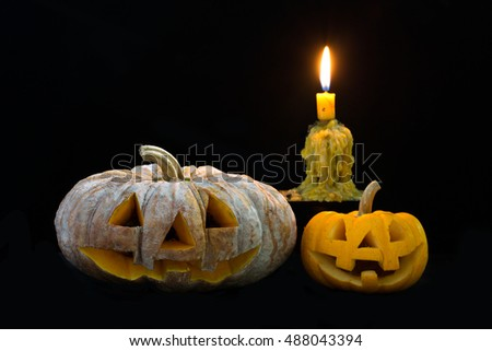 Halloween pumpkin with candle and candle light on the black table / Selective focus