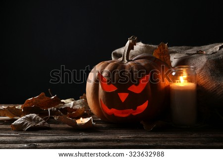 Halloween pumpkin with candle on brown wooden table - stock photo