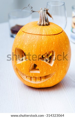 Halloween pumpkin with carved face on holiday table - stock photo