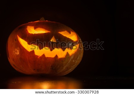Halloween pumpkin with scary face on black backgound - stock photo