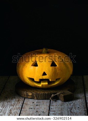 Halloween pumpkin with scary face on wooden background