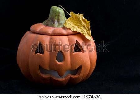 halloween pumpkin with yellow leaf on black - stock photo