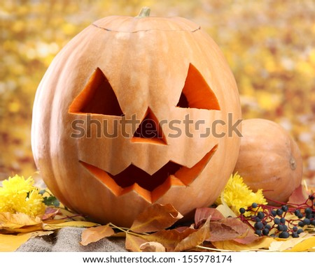 halloween pumpkins and autumn leaves, on yellow background - stock photo