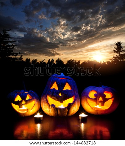 Halloween pumpkins glowing inside at forest and sunset evening sky background - stock photo