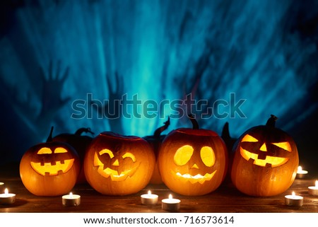 Halloween pumpkins in a row with candles over blue light rays and smoke with human hands silhouette at background, front view