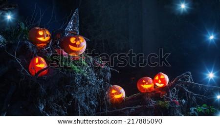 Halloween pumpkins in forest - stock photo
