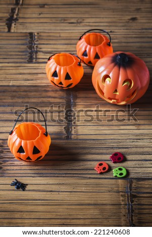 Halloween pumpkins on wooden with spider and skulls - stock photo