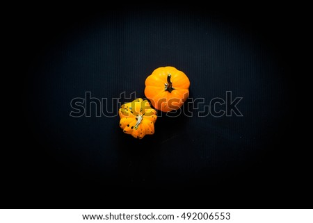 Halloween pumpkins, spiders and various objects on wooden background