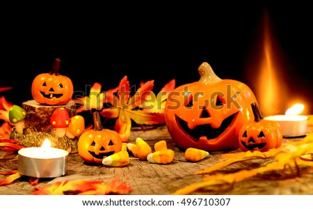Halloween pumpkins toy with fake candy on wood over black background