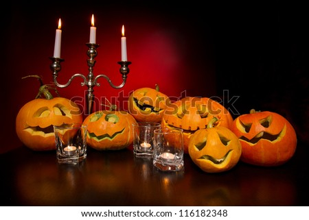Halloween pumpkins with candelabra on a wooden desk over red background - stock photo