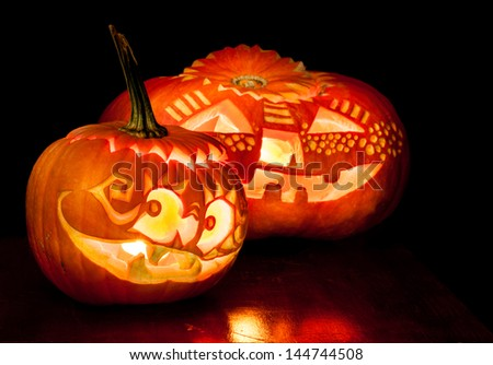 Halloween pumpkins with candles inside on black background - stock photo