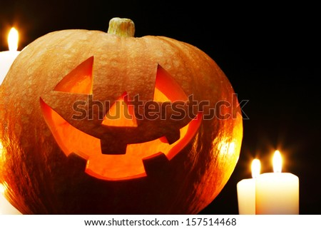 Halloween pumpkins with candles on black background - stock photo