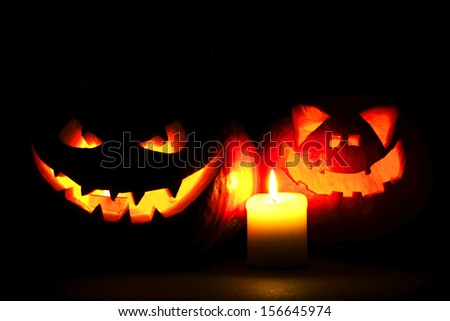Halloween pumpkins with scary face and burning candle on black background