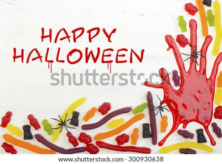Halloween rustic white wood background with bloody hand prints and candy, with Happy Halloween text.  - stock photo