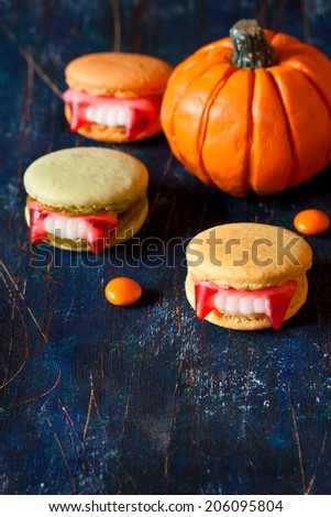 Halloween scary cookies with vampire teeth and pumpkin on dark blue board with copy space. - stock photo